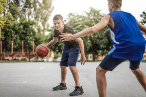 Teenagers playing basketball outdoors