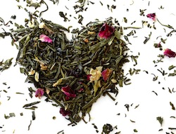 Green tea with flowers heart shape on white background