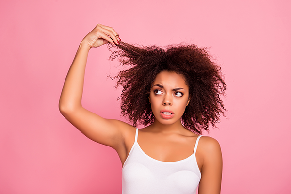 woman in front of a pink background tugging at a lock of hair
