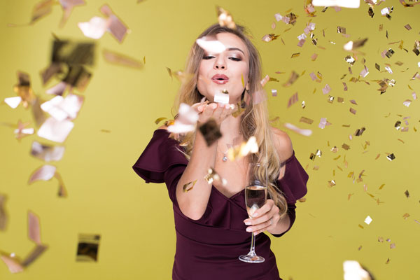 Woman blowing confetti in celebration of new year
