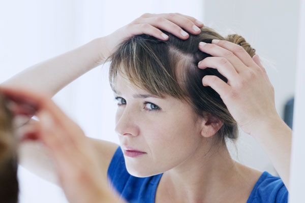 Woman looking at a bald spot on her scalp in the mirror