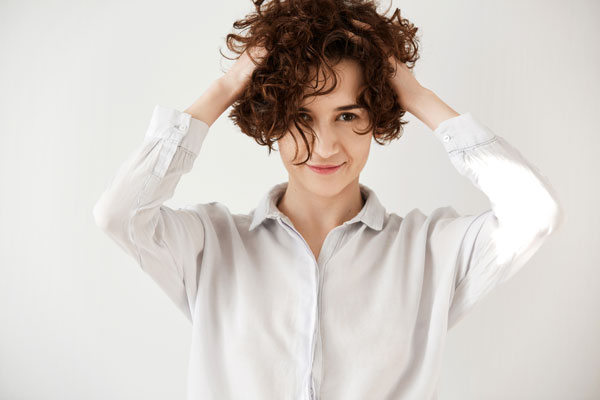Woman applying mousse into short curly hair