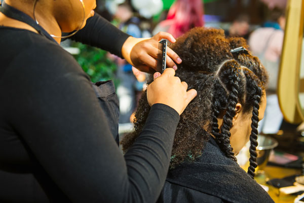 hairstylist sectioning off hair to add braids