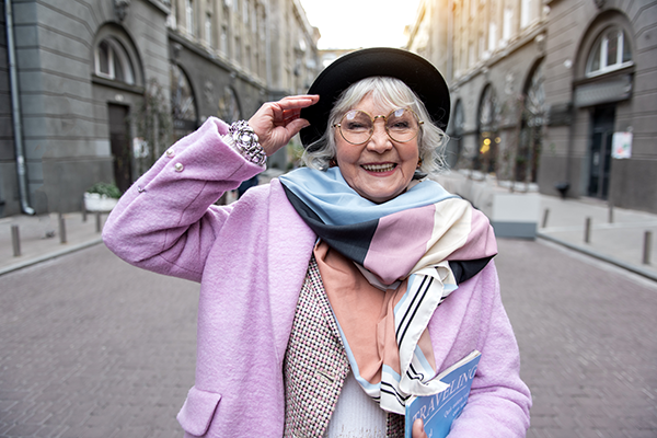 woman with gray hair wearing stylish outfit with purple coat and scarf with hat on in urban setting