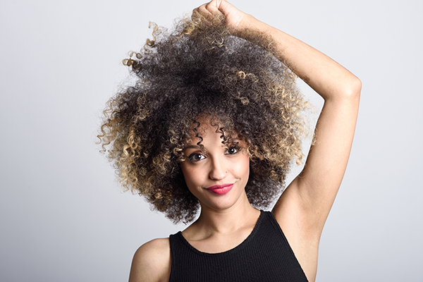 woman with coarse brittle curly hair touching afro