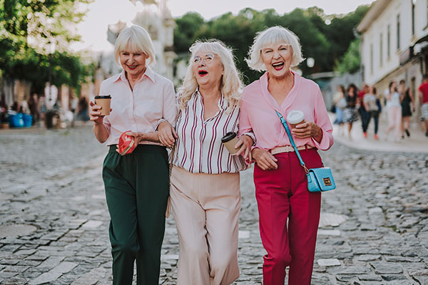 three women with white hair walking down the street with arms interlocked