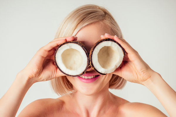 Beautiful young blonde haired girl with coconuts in her hand in the studio on a white background.