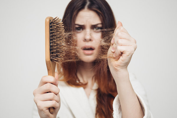 worried girl holding hairbrush filled with her hair
