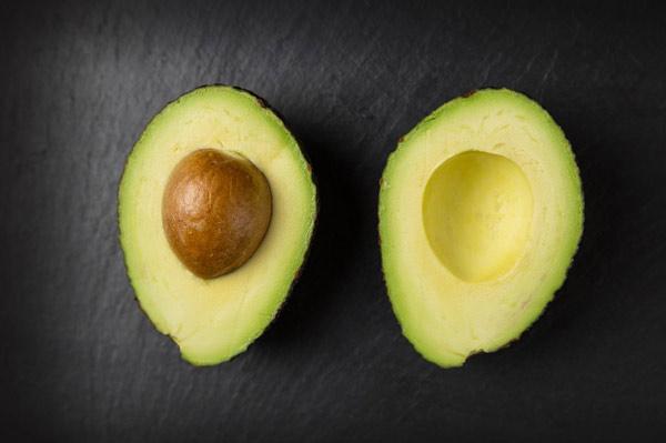 cut avocado on a black surface