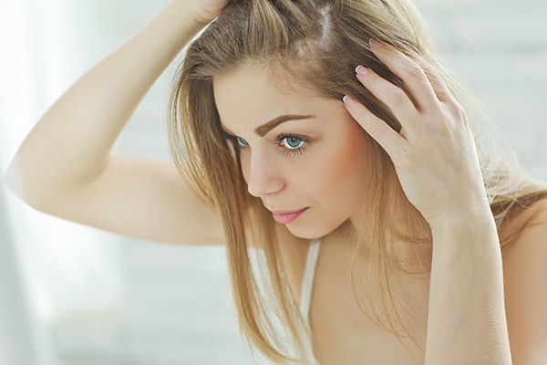 woman looking at scalp in the mirror