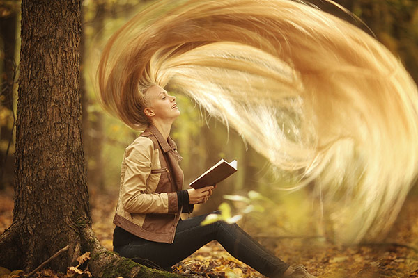 woman with very long blonde hair reading a book in the woods