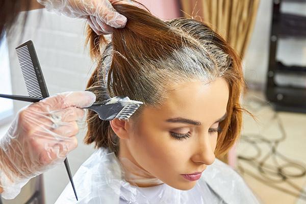 woman at hair salon with hair dye in her hair