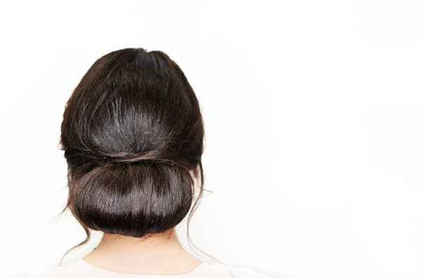 woman with brown hair with a low messy bun