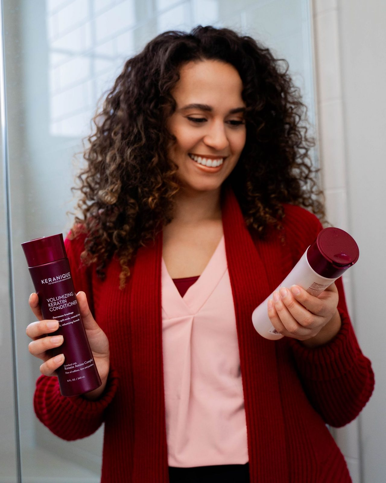 women looking at the shampoo and conditioner from Keranique