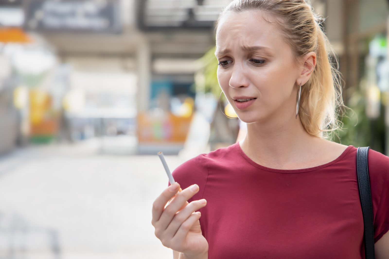 Determined woman trying to quit smoking and breaking her cigarette and cigarette.