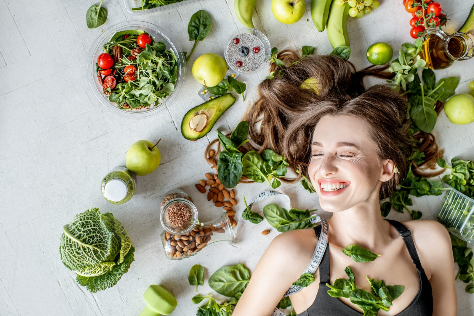Beauty portrait of a woman surrounded by various healthy food lying on the floor.