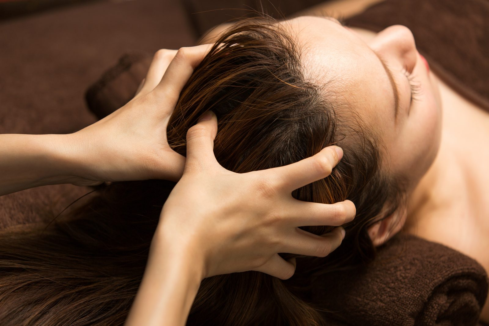 Hands massaging a woman's scalp to stimulate hair regrowth.