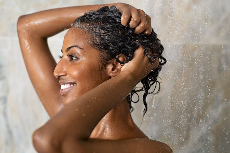 Women in the shower washing her hair with both hands.