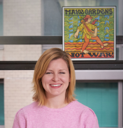 "Photo of staff member Alison Baldree in front of poster reading ""Make Gardens Not War"""