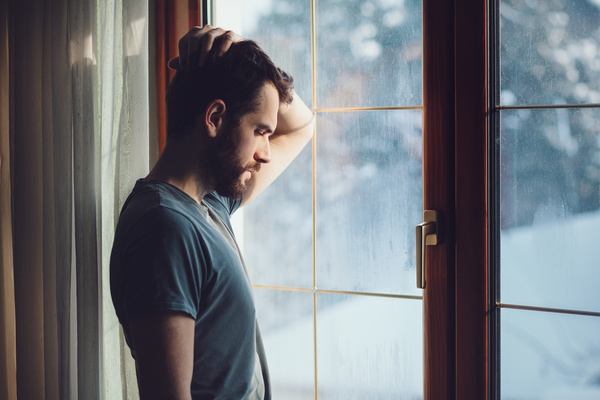 Image of a man near a window in winter to illustrate an article on how to fight depression in winter