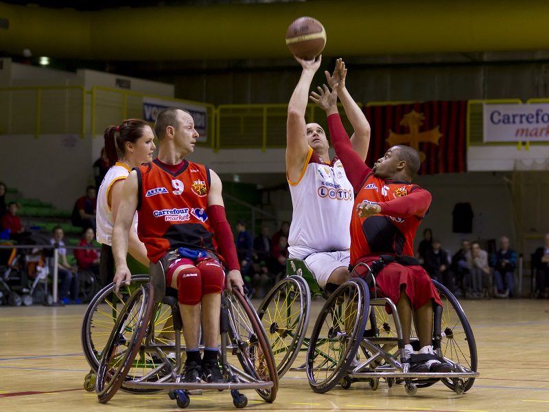 People who use wheelchairs playing basketball.