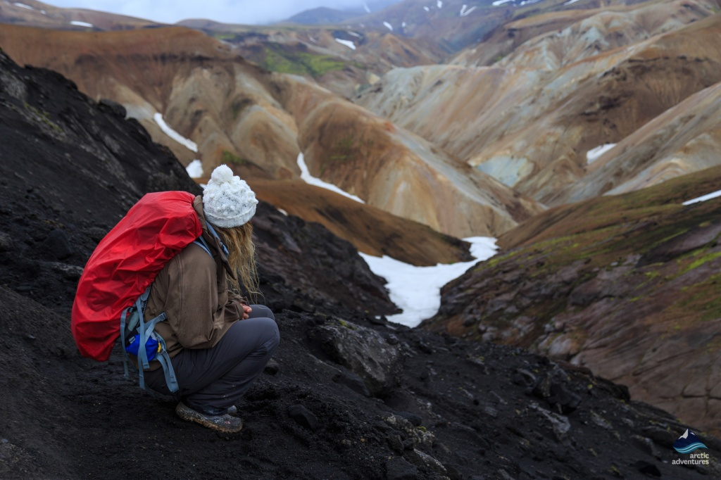 Girl sitting and looking out over Landmannalaugar, Iceland