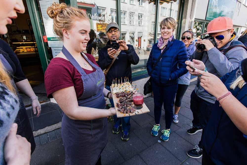 Woman offering food samples on Reykjavik food walk