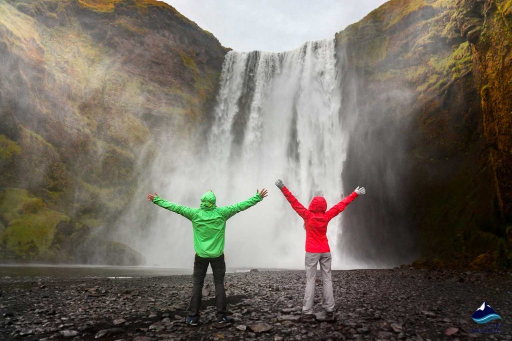 People by Skogafoss waterfall on Iceland golden circle. Couple visiting famous tourist attractions and landmarks in Icelandic nature landscape.