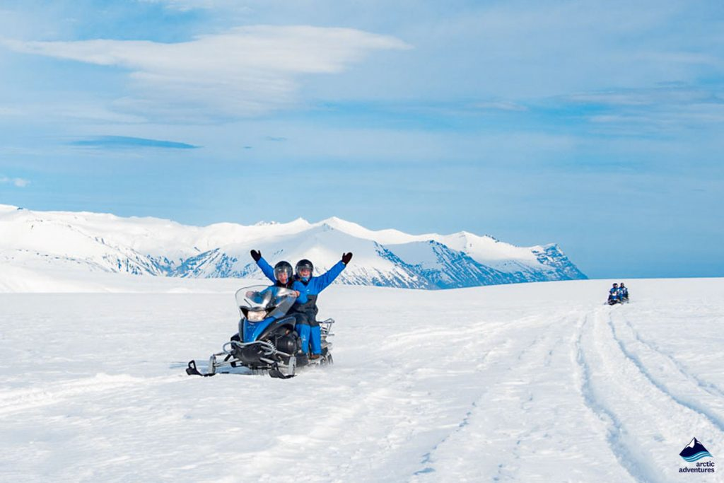 Happy people snowmobiling