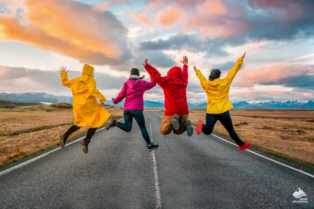 four friend jump on the road at sunset in Iceland