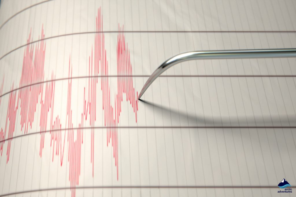 Seismograph machine needle drawing a red line on graph paper depicting seismic and eartquake activity