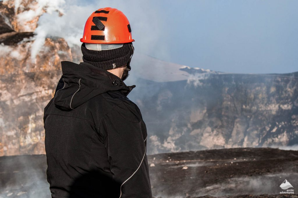 Geologist looks at the craters of the erupting volcano