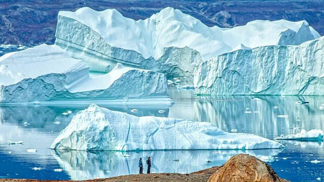 Hikers in front of large icebergs