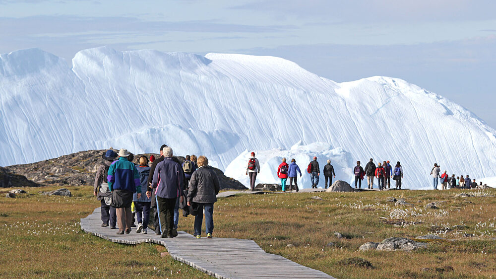 Hiking group on Ilulissat boardwalk with icebergs