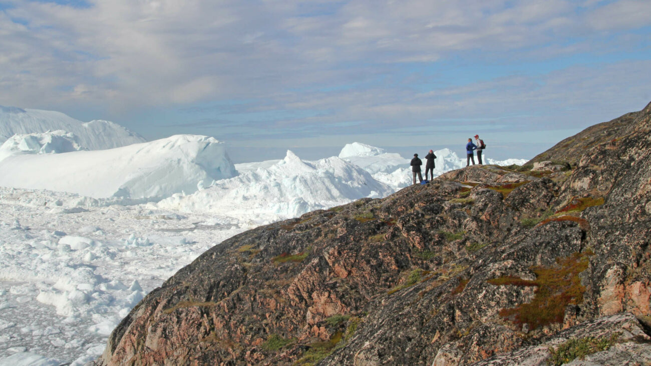 People on rocky outcrop ilulissat icefjord