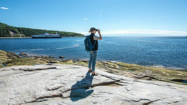 Day 2 woman looks with binoculars tadoussac whales