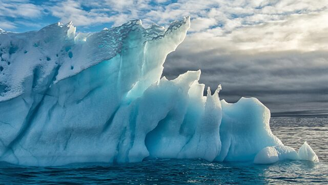 Turquoise iceberg cloudy skies