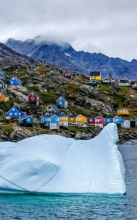 Iceberg in front of houses of Tasiilaq Sermersooq Greenland
