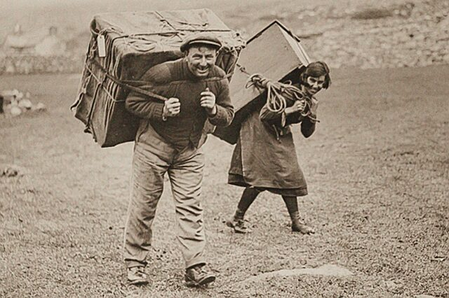 Historical photo departing St Kilda locals carrying trunks on their backs