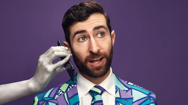 A silver hand holds a phone up to the ear of a bearded man in a colorful suit, against a purple background.