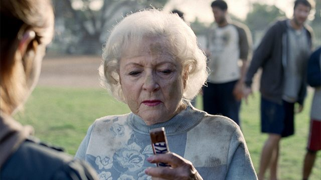 Betty White is looking at a Snickers bar as she seems like she is about to take the first bite