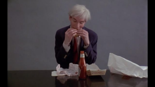 Andy Warhol eating a Burger King cheese burger