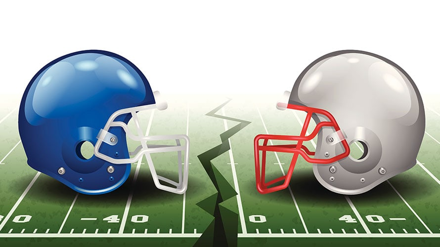 two large football helmet facing each other on a football field; in between them is a split in the field