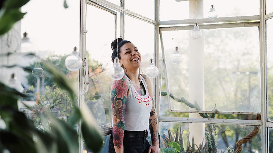 A woman stands near a window laughing with joy