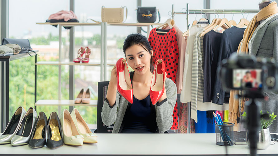 a woman is sitting at a desk; she is surrounded by clothing; in each hand is a high heel