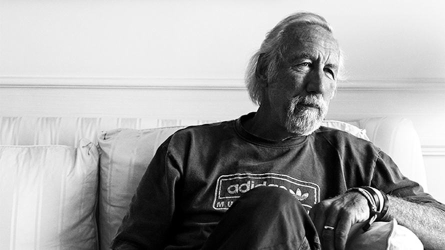 black and white photo of Lee Clow sitting on a couch