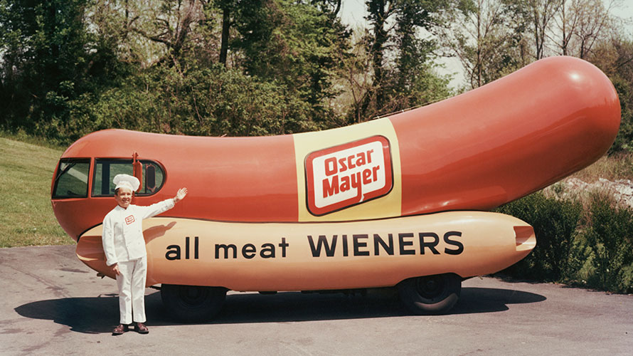 The renowned Oscar Mayer Wiener car that is shaped like a hot dog; next to the car is a chef pointing to the car