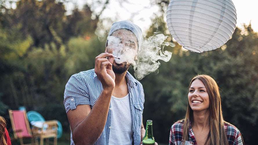 there is a couple in the image; the man holds a beer in one hand; in the other hand the man holds a cannabis cigarette and exhales a large cloud of smoke