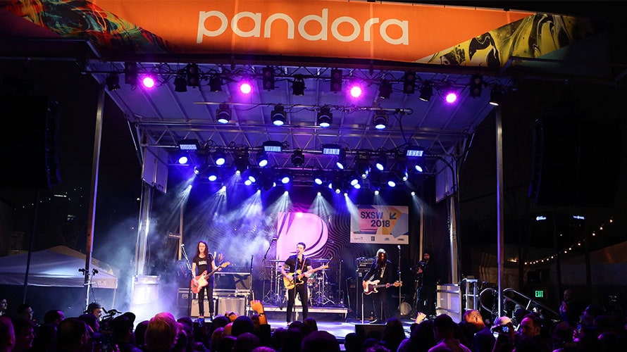 A band plays on stage in front of a packed crowd; on the stage there is a Pandora banner