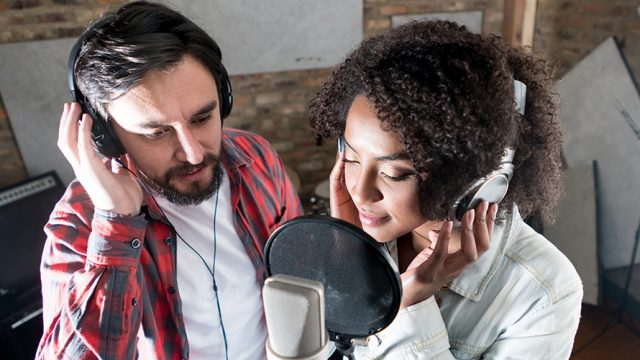 two people are standing side by side with headphones on; they appear to be singing into a recording studio's microphone